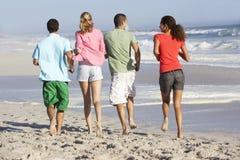 Jeunes amis marchant le long de la plage Photographie stock libre de droits
