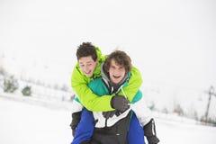 Jeunes amis masculins appréciant sur le dos le tour dans la neige Image libre de droits