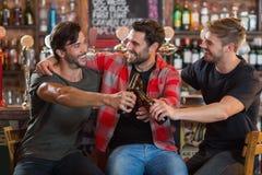 Jeunes amis masculins heureux grillant des bouteilles à bière dans la barre Image stock