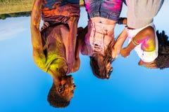 Jeunes amis multi-ethniques avec la peinture colorée sur des vêtements ayant l'amusement ensemble au festival de holi Photos stock