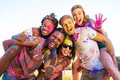 Jeunes amis multi-ethniques avec la peinture colorée sur des vêtements ayant l'amusement ensemble au festival de holi Images libres de droits