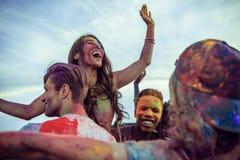 Jeunes amis multi-ethniques avec la peinture colorée sur des vêtements et des corps ayant l'amusement ensemble au festival de hol Photo stock