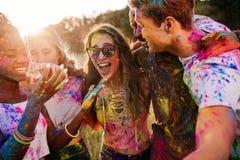 Jeunes amis multi-ethniques avec la peinture colorée sur des vêtements et des corps ayant l'amusement ensemble au festival de hol Photographie stock