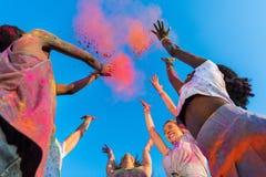 Jeunes amis multi-ethniques ayant l'amusement avec la poudre colorée au festival de holi de couleurs Photographie stock