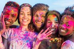 Jeunes amis multi-ethniques ayant l'amusement avec la poudre colorée au festival de holi de couleurs Images stock