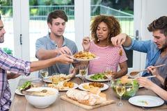 Jeunes amis multi-ethniques ayant le repas à la table Photographie stock