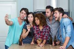 Jeunes amis multi-ethniques faisant des visages tout en prenant le selfie Photographie stock