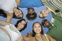 Jeunes amis multi-ethniques formant un cercle Images stock