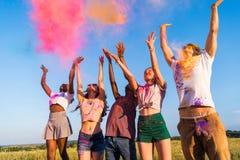 Jeunes amis multi-ethniques jetant la poudre colorée au festival de holi Image libre de droits