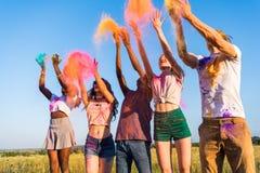 Jeunes amis multi-ethniques jetant la poudre colorée au festival de holi Images stock