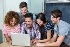 Jeunes amis multi-ethniques regardant dans l'ordinateur portable sur la table Photographie stock