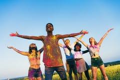 Jeunes amis multi-ethniques se tenant avec les bras ouverts au festival de holi de couleurs Photos stock