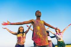 Jeunes amis multi-ethniques se tenant avec les bras ouverts au festival de holi de couleurs Photo libre de droits