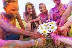 Jeunes amis multi-ethniques tenant des camomilles au festival de holi Image stock