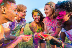 Jeunes amis multi-ethniques tenant la peinture colorée dans des mains au festival de holi Images stock