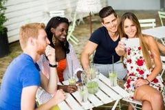 Jeunes amis multiraciaux au café Images libres de droits