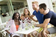 Jeunes amis multiraciaux au café Image libre de droits