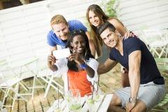 Jeunes amis multiraciaux en café Image libre de droits