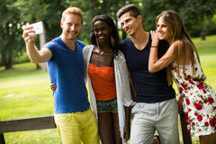 Jeunes amis multiraciaux en parc Photos libres de droits