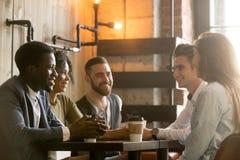 Jeunes amis multiraciaux parlant et buvant du café partageant la Co Image stock