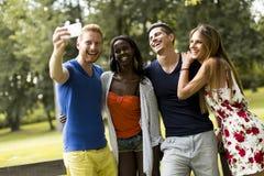 Jeunes amis multiraciaux prenant le selfie en parc Photos stock