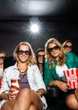 Jeunes amis observant le film 3D dans le théâtre Image stock