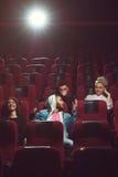 Jeunes amis observant le film dans le théâtre de cinéma Photographie stock