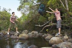 Jeunes amis par le sac à dos de lancement de rivière Photo stock