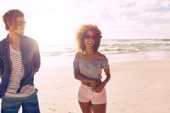 Jeunes amis parlant et riant sur une plage Image stock