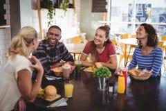 Jeunes amis parlant tout en se reposant à la table avec la nourriture et la boisson Images stock