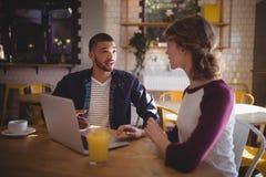 Jeunes amis parlant tout en se reposant avec l'ordinateur portable et les boissons Photos libres de droits