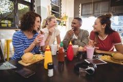 Jeunes amis parlant tout en se reposant avec la nourriture et la boisson au café Photos stock