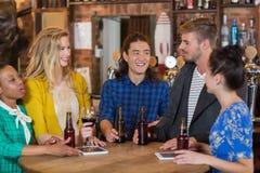 Jeunes amis parlant tout en se tenant prêt les comprimés numériques et les bouteilles à bière dans le bar Photos stock
