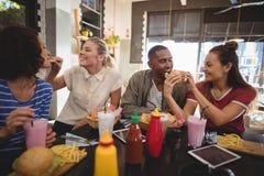 Jeunes amis partageant la nourriture au café Images libres de droits