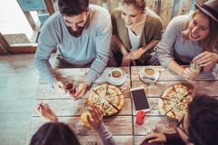 Jeunes amis partageant la pizza dans un café d'intérieur Photo stock