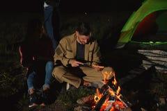 Jeunes amis passant le temps près du feu la nuit Photo stock