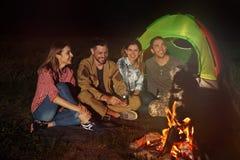 Jeunes amis passant le temps près du feu la nuit Photographie stock