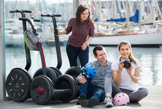 Jeunes amis posant près des segways sur le rivage Photos stock