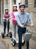Jeunes amis posant sur des segways sur la rue de ville Photographie stock