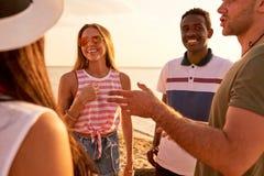 Jeunes amis positifs causant sur la plage Photo libre de droits