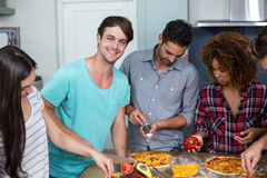 Jeunes amis préparant la pizza à la maison Photographie stock