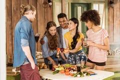 Jeunes amis préparant la salade végétale et buvant des verres sur le porche Photos stock