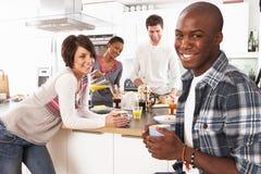 Jeunes amis préparant le déjeuner dans la cuisine Images libres de droits