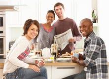 Jeunes amis préparant le déjeuner dans la cuisine Photos stock