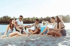 Jeunes amis prenant la bière du réfrigérateur portatif tout en se reposant sur la plage sablonneuse Images stock