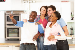 Jeunes amis prenant la photo dans la cuisine Images stock