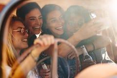 Jeunes amis prenant le selfie dans la voiture Image stock