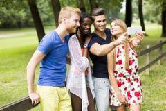 Jeunes amis prenant le selfie en parc Photos stock