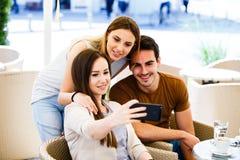 Jeunes amis prenant le selfie tout en se reposant au café Photo stock