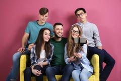 Jeunes amis prenant le selfie tout en se reposant sur le sofa Image stock